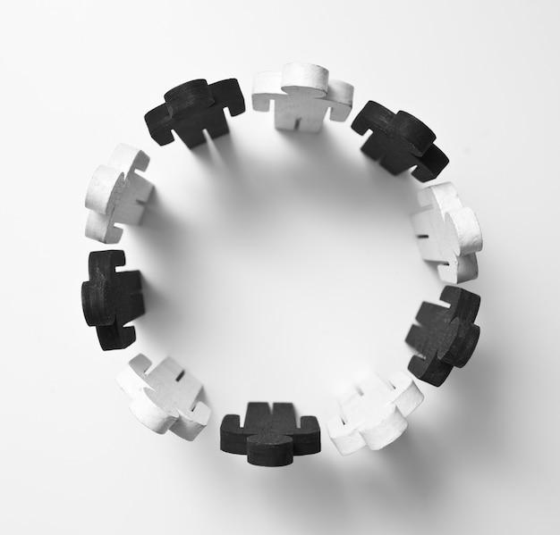 Houten figuren van personen zwart-witte kleur staan in een cirkel