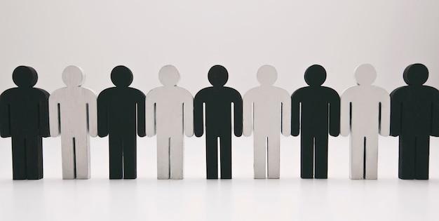 Houten figuren van persoon zwart-witte kleur staan in de rij. concept van vriendschap, teamwork en gebrek aan racisme