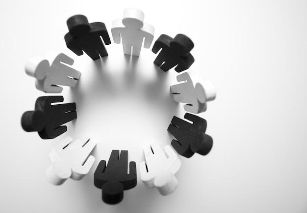 Houten figuren van persoon zwart-witte kleur staan in een cirkel