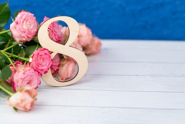 Houten figuur 8 met roze bloemen op een witte tafel. internationale vrouwendag. 8 maart