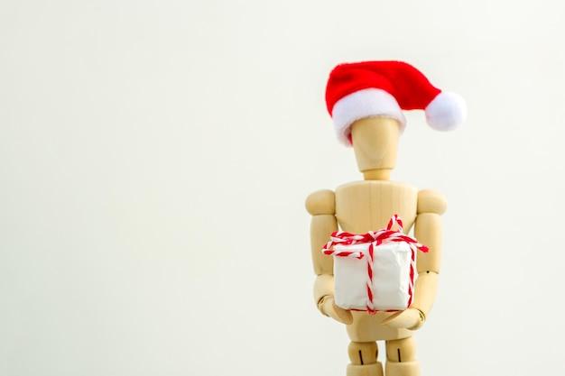 Houten figuur - kunst etalagepop met rode kerstmuts met geschenkdoos. bedrijfs- en ontwerpconcept voor kerstmis