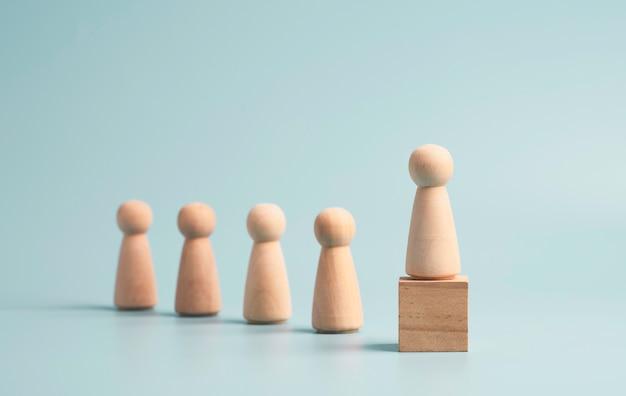 Houten figuur op houten kubusblok op blauwe achtergrond, promotie naar leiderschap en managementgroeiconcept.