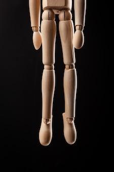 Houten figuur opgehangen met een touw geïsoleerd op zwart