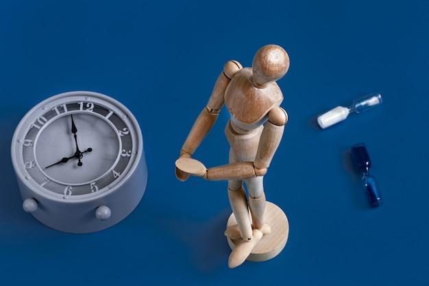 Houten figuur van een man op blauw met een klok