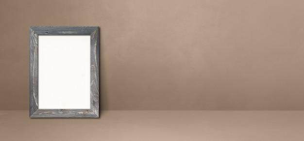 Houten fotolijst leunend op een beige muur. lege mockup-sjabloon. horizontale banner