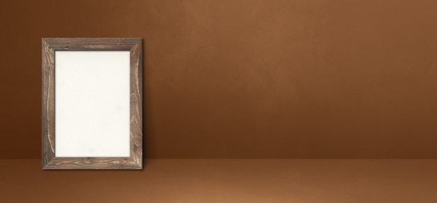 Houten fotolijst leunend op een bruine muur. lege mockup-sjabloon. horizontale banner