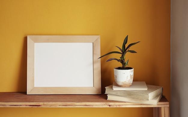 Houten fotolijst mockup. bloempot op een stapel boeken op een oude houten plank. samenstelling op een gele muur