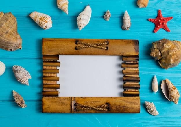 Houten fotolijst op blauw hout met verschillende zeeschelpen