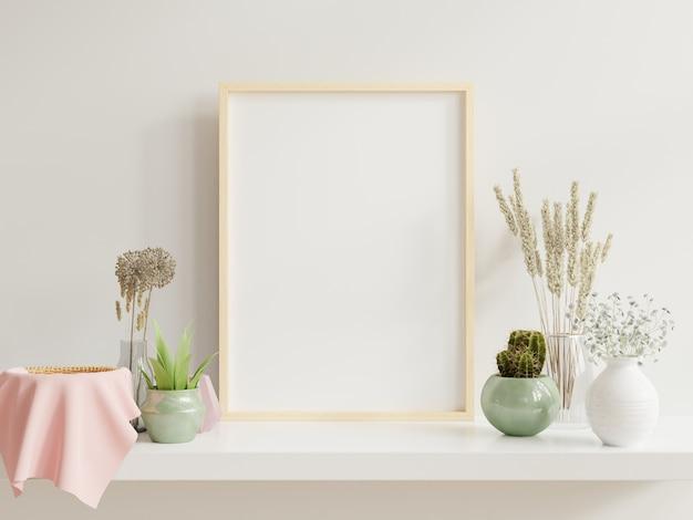 Houten frame leunend op witte plank in lichte interieur met planten op tafel met planten in potten op lege muur
