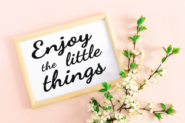 Houten frame met de inscriptie geniet van de kleine dingen, lente inspirerende en motiverende tekst en kersen takken met bloemen