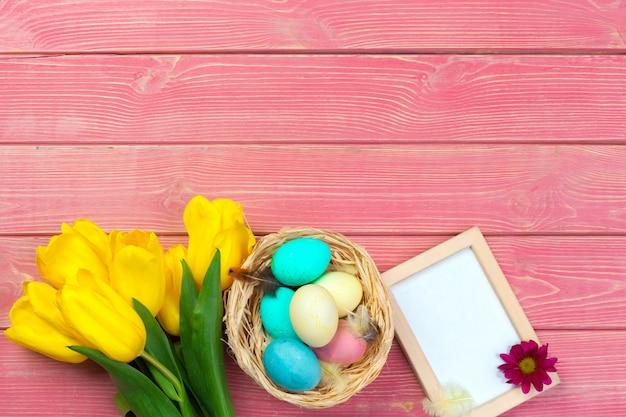 Houten frame met paaseieren en tulpen op kleurrijke achtergrond