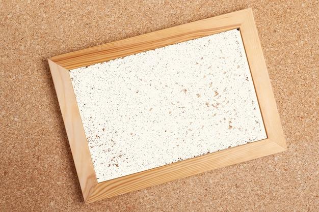 Houten frame met witte pagina op kurk boord