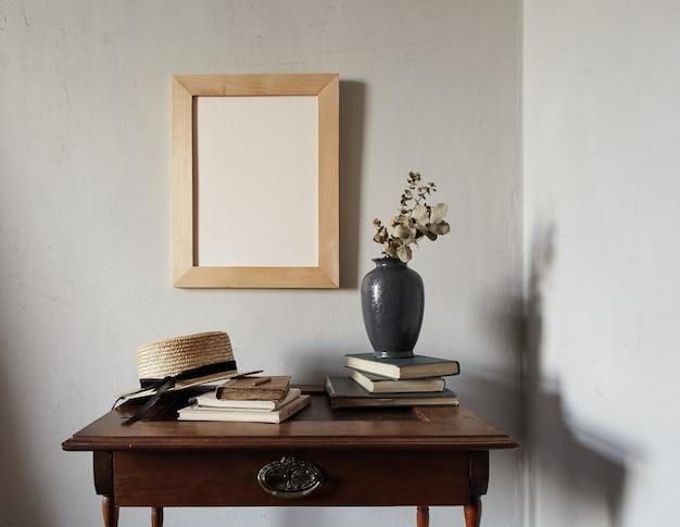 Houten frame mockup. compositie met notebook, boeken, vaas met gedroogde bloemen op een oude houten tafel. modern frans interieur.