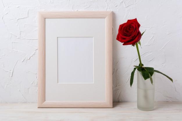 Houten frame mockup met rode roos in glazen vaas