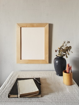 Houten frame mockup. scandinavisch minimalistisch design. bloempot op een stapel boeken op een oud houten bureau. samenstelling op een witte muur