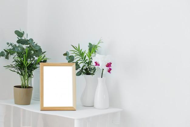 Houten frame op vintage witte plank met bloemen en planten
