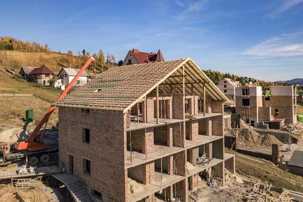 Houten frame van nieuw dak op een baksteen groot huis in aanbouw.