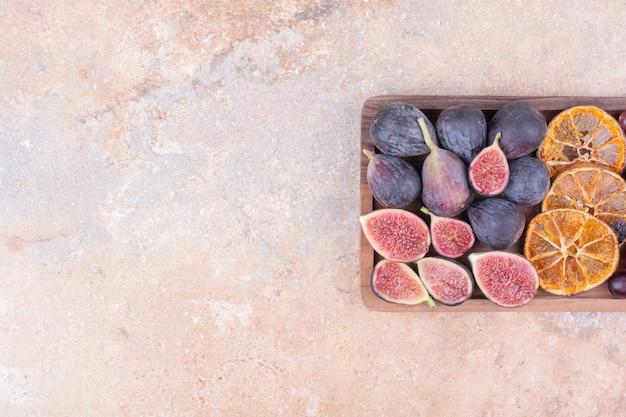 Houten fruitschaal met vijgen en droge stukjes sinaasappel.