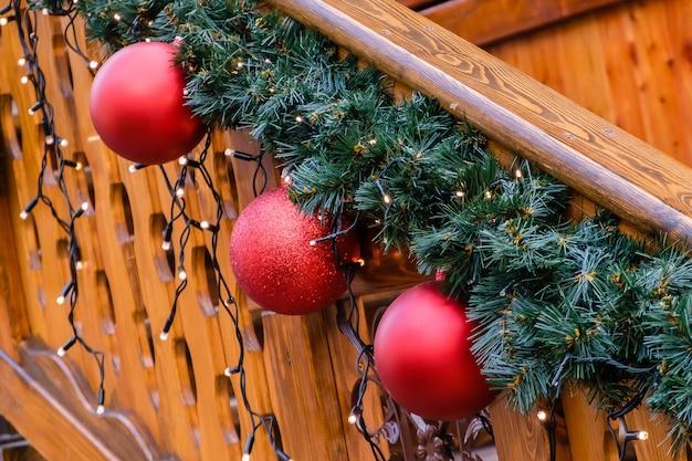 Houten gebouw versierd met kunstmatige dennenboom met guirlande en veel rode kerstballen