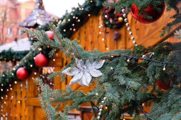 Houten gebouw versierd met kunstmatige dennenboom met lichtslinger en veel rode kerstballen