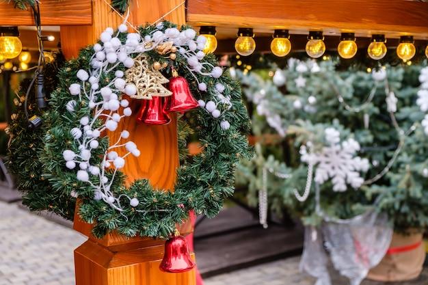 Houten gebouw versierd met kunstmatige dennenboom met verlichtingsslinger en veel rode kerstklokken