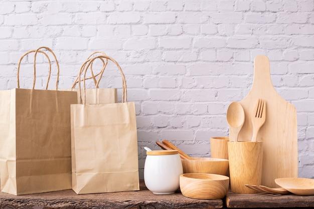 Houten gebruiksvoorwerpen en boodschappentassen op houten tafel.