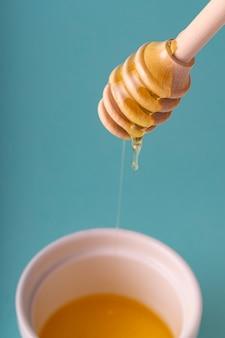 Houten gecanneleerde lepel met druipende honing