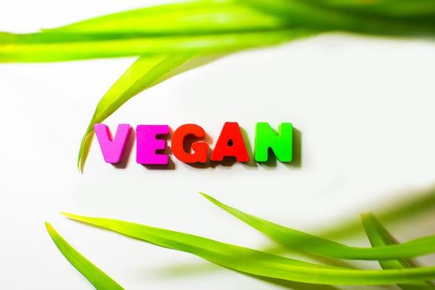 Houten geïsoleerd tekstwoord vegan met verse plantenbladeren