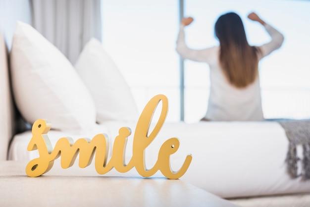 Houten gele glimlachtekst met haar vrouw die op bed opstapt