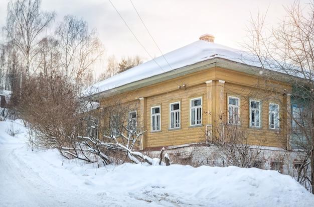 Houten gele huizen op een met sneeuw bedekte heuvel in plyos in het licht van een winterse dag onder een blauwe hemel