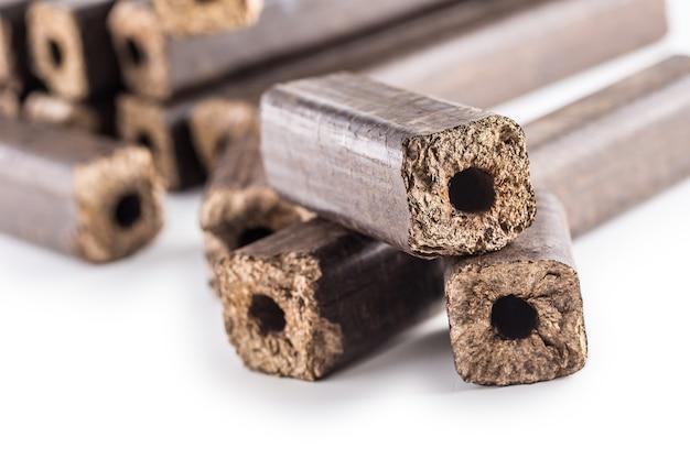 Houten geperste briketten pini kay uit biomassa op een witte geïsoleerde achtergrond.