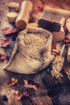 Houten geperste korrels en briketten uit biomassa met herfstbladeren.