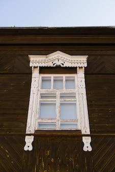 Houten gesneden raamkozijn in een houten russisch huis
