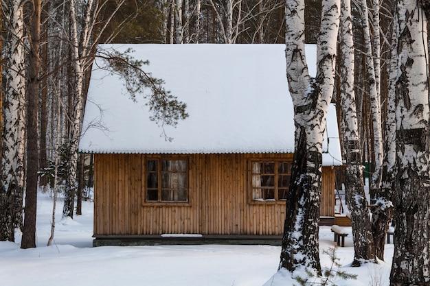 Houten gezellige huis in een besneeuwde bos. leuke kerstsfeer