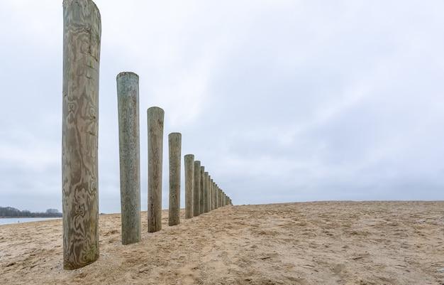 Houten golfbrekerpalen op een strand onder een bewolkte hemel overdag