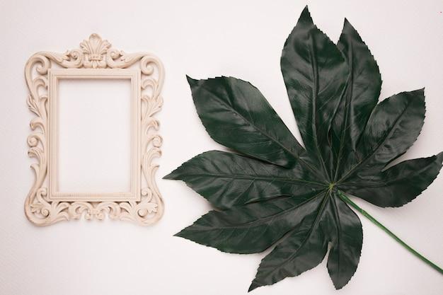 Houten gravure kader dichtbij het groene kunstmatige blad op witte achtergrond