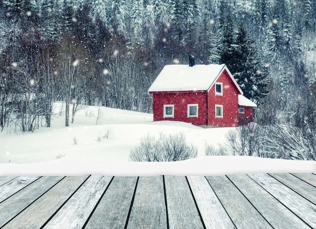 Houten grijs met rood huis in het sneeuwen op de winter