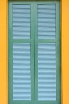 Houten groene deur vintage huis en gele muur