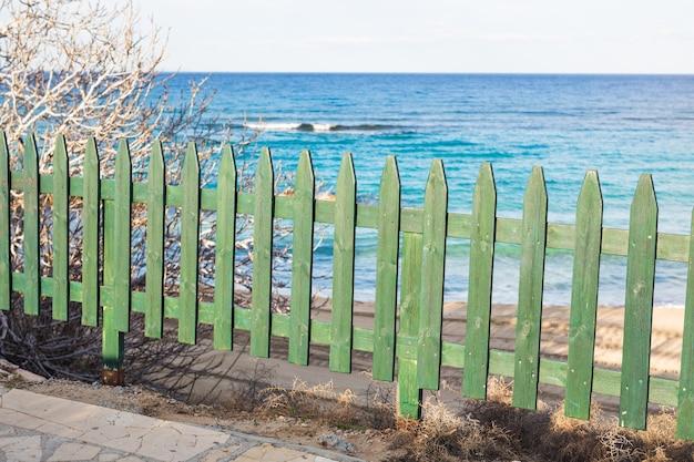 Houten groene omheining op het zeestrand