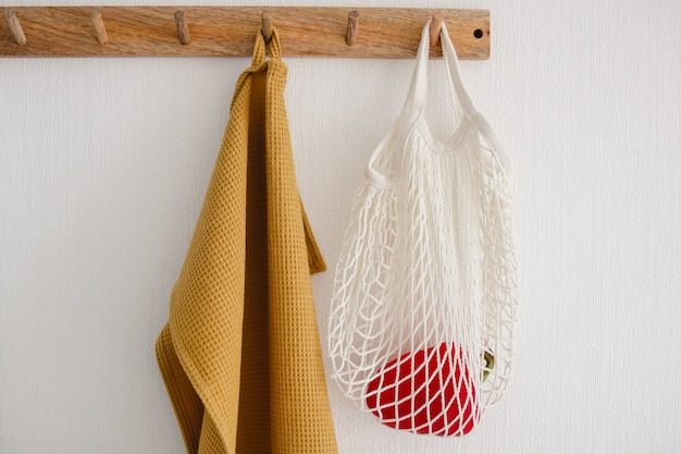 Houten haakhanger met witte eco tas met een paprika en een gele katoenen handdoek, hangend aan een witte muur in de moderne keuken