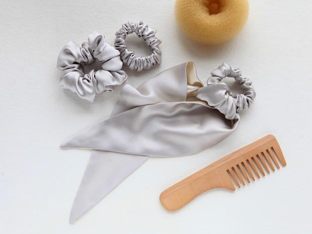 Houten haarborstel haarspeldje en zijde zilver scrunchy op wit plat leggen kappersaccessoires