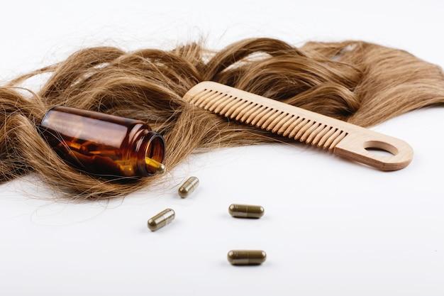 Houten haarkam en fles met vitamines liggen op krullen van bruin haar