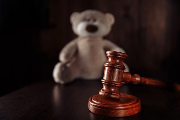 Houten hamer en teddybeer als bescherming van symboolkinderen