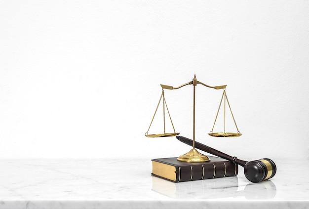 Houten hamer en wetsboek gezet op witte marmeren lijst hoogste teller