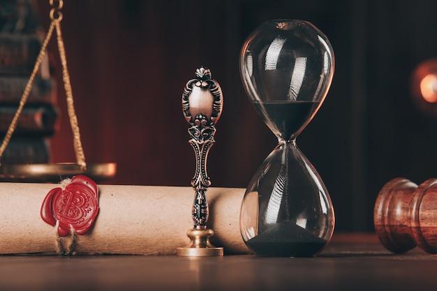 Houten hamer, zandloper en antieke stempel met laatste wil op houten tafel close-up