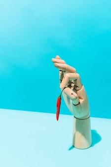 Houten hand met een rode peper op een blauwe achtergrond mexicaans eten