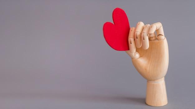 Houten hand met rood hart