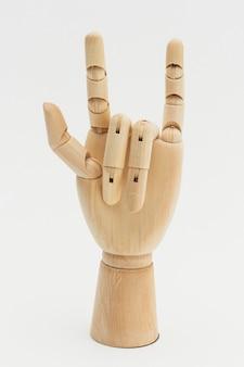 Houten hand toont liefdesymbool op gebroken wit
