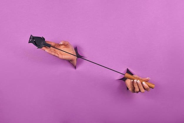 Houten handboeien zijn een seksspeeltje op een roze achtergrond in de handen van een vrouw