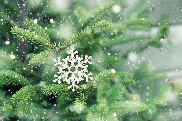Houten handgemaakte sneeuwvlok opknoping op groene kerstboom terwijl het sneeuwt